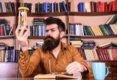 Man on busy face reading book, bookshelves on background. Lesson and time concept. Teacher or student with beard. Studying in library. Scientist with eyeglasses Stock Images