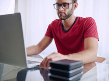 Man busy inserting a memory stick into his notebook Stock Photography