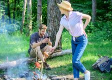 Man busy with smartphone while girl roasting food over fire. Family picnic nature background. Even at vacation he stay stock photo