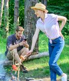 Man busy with smartphone while girl roasting food over fire. Family picnic nature background. Family relaxing at picnic royalty free stock photos