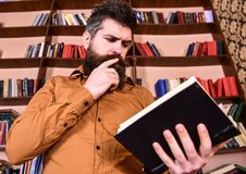 Man on busy thoughtful face reading book, bookshelves on background. Education and science concept. Teacher or student. With beard studying in library Stock Photo