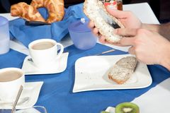 Man buttering his roll at breakfast Stock Photography