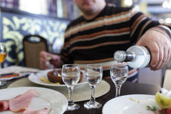 Man buttles vodka in a taverna Royalty Free Stock Photography