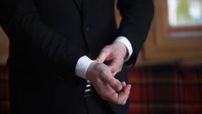 Man buttoning on a black jacket. Wedding details - elegant groom dressed wedding tuxedo costume is waiting for the bride Royalty Free Stock Photography