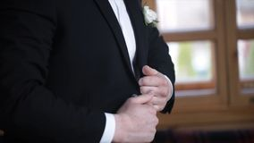 Man buttoning on a black jacket. Wedding details - elegant groom dressed wedding tuxedo costume is waiting for the bride Royalty Free Stock Photo