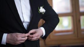 Man buttoning on a black jacket. Wedding details - elegant groom dressed wedding tuxedo costume is waiting for the bride Stock Images