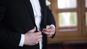 Man buttoning on a black jacket. Wedding details - elegant groom dressed wedding tuxedo costume is waiting for the bride Stock Photos