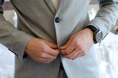 Buttoning. Man buttoning a gray jacket, hand with black watch Stock Image