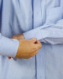 Man buttoning his shirt Stock Photography