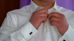 Dressed man. Man buttoning shirt. Man buttoning shirt closeup. Dressed man stock footage