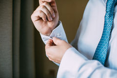 Man buttoning on the sleeve of his shirt. Zip up the cufflink Royalty Free Stock Photo