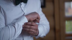 Man buttoning on the sleeves of the shirt. Close up of a hand man how wears white shirt and cufflink. Man buttoning on. The sleeve of his shirt. Zip up the stock images