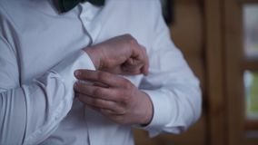 Man buttoning on the sleeves of the shirt. Close up of a hand man how wears white shirt and cufflink. Man buttoning on. The sleeve of his shirt. Zip up the stock image