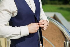 Man buttoning vest of blue suit Stock Photo