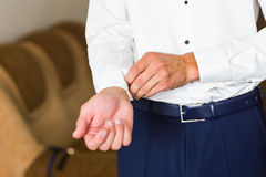 Man buttons cuff-link on French cuffs sleeves luxury white shirt Royalty Free Stock Photo