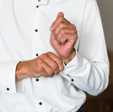 Man buttons cuff-link on French cuffs sleeves luxury white shirt Royalty Free Stock Images