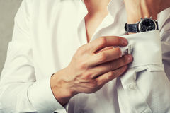 Man buttons cuff-link on French cuffs. Sleeves luxury white shirt. Tonal correction stock image