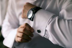 Man buttons on the hand cuffs to the clock. Man in white shirt buttons on the hand cuffs to the clock Royalty Free Stock Photography
