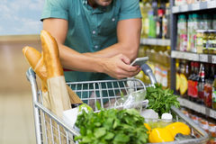 Man buy products and using his smartphone Royalty Free Stock Photos