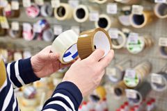Man buyer chooses adhesive duct tape in store. Man buyer chooses the adhesive duct tape in the store royalty free stock image