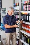 Man Buying Alcohol At Supermarket. Happy senior man buying alcohol at supermarket Stock Photo