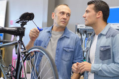 Man buying bike saddle in bike shop Royalty Free Stock Photo
