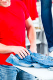 Man buying blue jeans Stock Photography