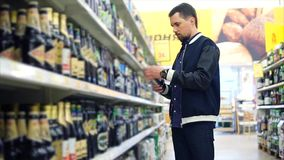 Man buying a bottle of beer in the supermarket stock video