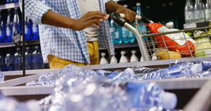 Man buying bottle of water at grocery section