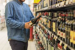 Man buying wine. Man is buying a bottle of wine at the liquor market stock image