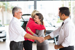Man buying car daughter. Senior men buying car for his daughter handshaking with dealer after the sale Royalty Free Stock Photography