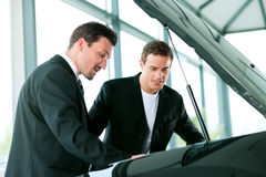 Man buying car from salesperson. Man buying a car in dealership looking under the hood at the engine Stock Images