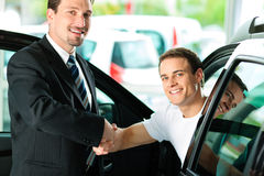 Man buying car from salesperson. Man buying a car in dealership sitting in his new auto; they are shaking hands to close the deal Stock Photo