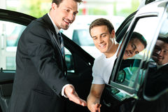 Man buying car from salespersonv. Man buying a car in dealership sitting in his new auto, the salesman talking to him and explaining details Royalty Free Stock Photo