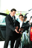 Man buying car from salespersonv. Man buying a car in dealership sitting in his new auto, the salesman talking to him and explaining details Stock Photography