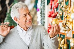Man Buying Christmas Baubles At Store Royalty Free Stock Photos