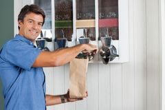 Man Buying Coffee Beans At Grocery Store. Portrait of mid adult man buying coffee beans from vending machine at grocery store royalty free stock photo