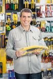 Man Buying Handsaw In Hardware Store Royalty Free Stock Image