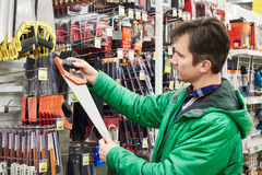 Man buying handsaw in store Royalty Free Stock Image