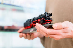 Man buying model railroad in toy store. Holding the model in his hands, close-up Royalty Free Stock Photography