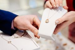 Man buying necklace in jewelry store. Sale and customer service in the store Royalty Free Stock Images