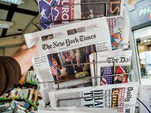 Man buying The New York Times newspaper at press kiosk. PARIS, FRANCE - JUNE 13, 2018: Man buying The New York Times newspaper at press kiosk showing on cover U royalty free stock photography