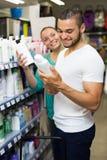 Man buying shampoo. Smiling men buying shampoo in shopping mall royalty free stock photo