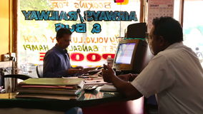 Man buying a ticket at bus and railway ticket office in Goa. stock footage