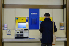 A man buying ticket at machine in Tokyo subway station Stock Photography