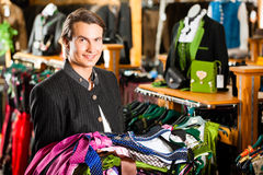 Man is buying Tracht or dirndl in a shop Stock Photos