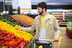 Man buying vegetables in organic shop Stock Photos