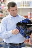 Man buying welding mask in hardware store Stock Image