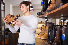 Man buying winter shoes. Happy man buying winter shoes in a shoe shop stock photos