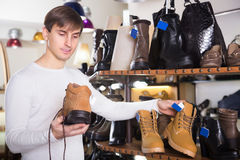 Man buying winter shoes. Happy man buying winter shoes in a shoe store royalty free stock photography